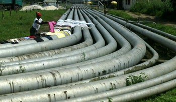 Woman lays clothes out to dry on an oil pipeline running through the Okrika neighborhood of Port Harcourt in Nigeria's oil-rich delta region, Saturday, Oct. 7 2006.