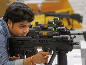 FILE Photo: A man examines an assault rifle manufactured by Israel Weapons Industries in New Delhi, India, April 1, 2012.