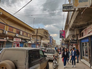 People walking down the street in Qamishli, northern Syria, with storefronts featuring signage in various languages.