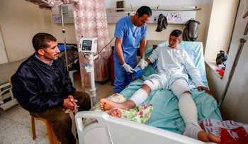 Palestinian teenager Osama Hajajeh receives treatment as his father watches, Beit Jala, West Bank, April 23, 2019.