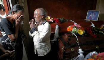 People mourn next to coffins of their relatives killed in an explosion at St. Anthony's Shrine, Kochchikade church on Easter Sunday, Colombo, Sri Lanka April 23, 2019.