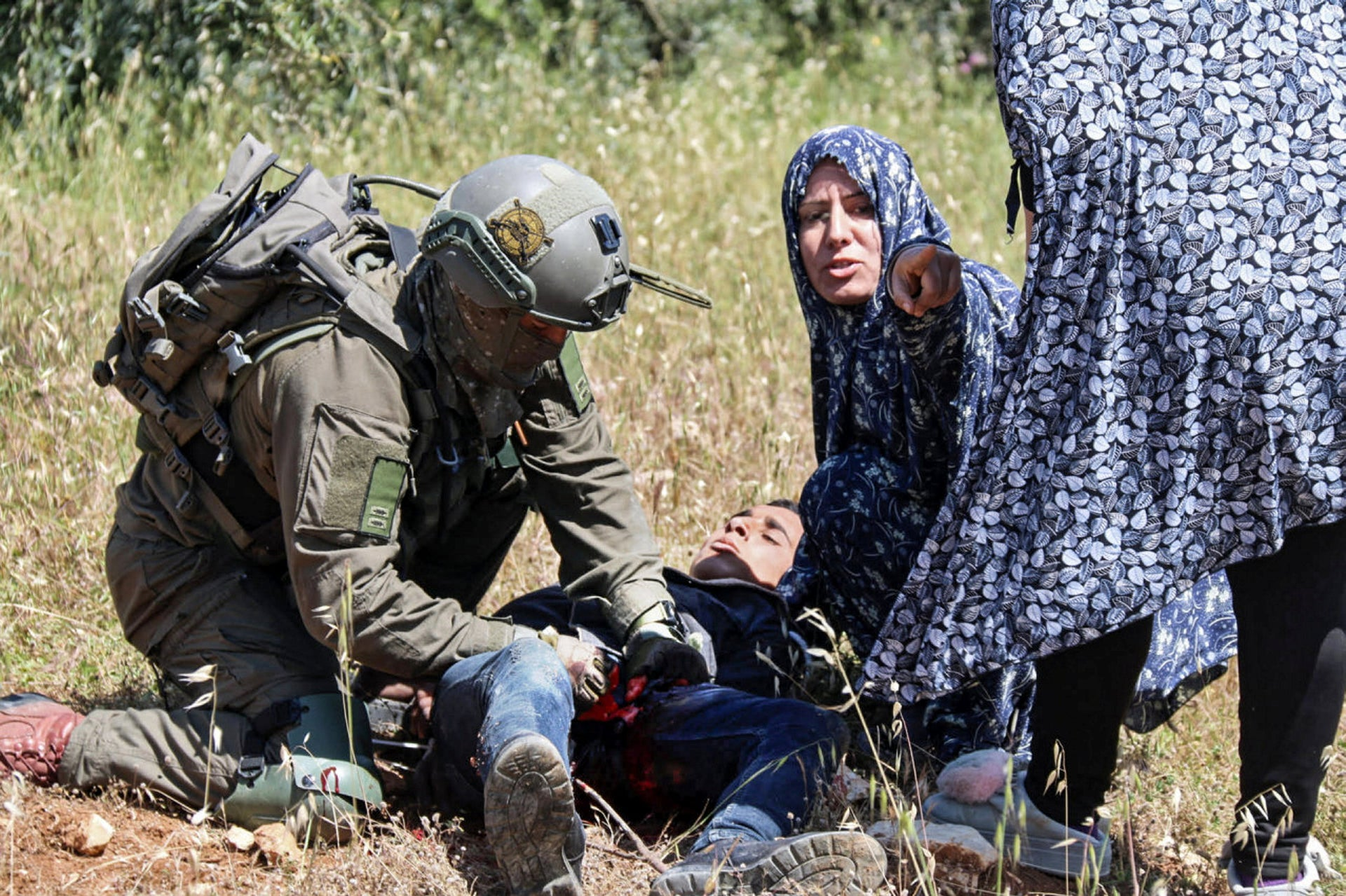 Osama Hajajeh is tended by a medic and two women from his village after being shot by Israeli soldiers, Tuqu, April 18, 2019.