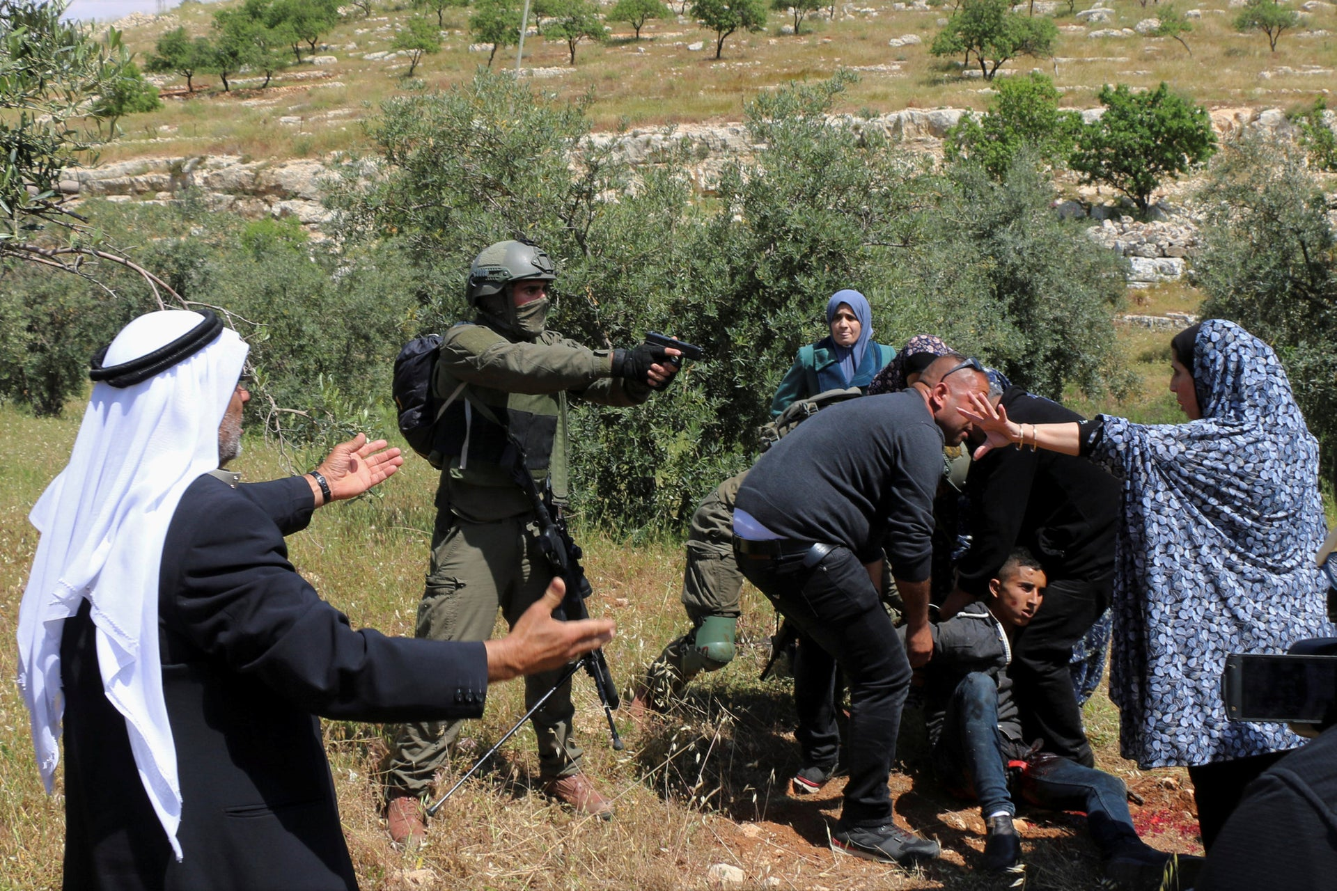 An Israeli soldier points his pistol at a group of Palestinians gathering around Osama Hajahjeh, who was shot by IDF troops.