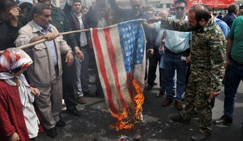 Protesters burn a U.S. flag during a rally against the U.S.'s decision to designate Iran's powerful Revolutionary Guards as a terrorist organization, Tehran, Iran, Friday, April 12, 2019.