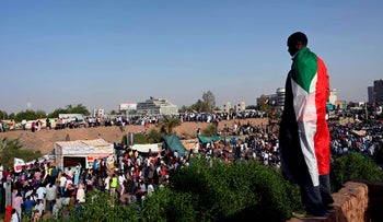 "A Sudanese protester stands on a hill overlooking fellow demonstrators as they gather for a ""million-strong"" march outside the army headquarters in the capital Khartoum on April 25, 2019."