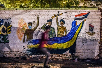 A Sudanese protester runs past a recently painted mural during a demonstration near the army headquarters in the capital Khartoum on April 24, 2019.