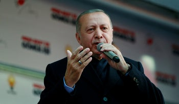 Turkish President Tayyip Erdogan addresses supporters in Ankara during a rally ahead of the local elections, on March 28, 2019.