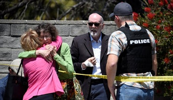 Two people hug as another talks to a San Diego County Sheriff's deputy outside of the Chabad of Poway Synagogue Saturday, California, April 27, 2019.