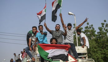 Sudanese protesters, sitting atop a bus, arrive to join the sit-in outside the army headquarters in the capital Khartoum, April 27, 2019.