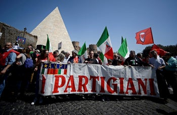"""Demonstrators hold a banner reading """"Partisans""""by Rome's Cestia Pyramid on April 25, 2019 during a march marking Liberation Day and the overthrow of Mussolini's WWII fascist regime"""