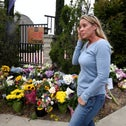 A woman wipes a tear from her eye after putting flowers on a memorial at the Chabad of Poway synagogue, in Poway, Calif., Sunday, April 28, 2019.