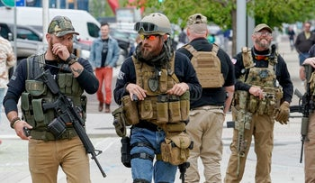 Members of a militia organization walk down the street near the site of the National Rifle Association's (NRA) annual meeting, in Indianapolis, Indiana, U.S., April 27, 2019.