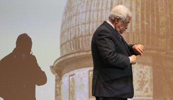 FILE PHOTO: Palestinian President Mahmoud Abbas checks his watch before a speech in the West Bank city of Ramallah on January 4, 2015