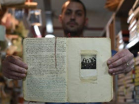 Nir Itzik, an archivist at the Moreshet archive in Israel, holding aloft the original copy of Judit Ornstein's wartime diary.