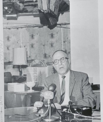 Rabbi Perry Nussbaum talks with newsmen on in his living room with boarded up windows, bombed the day before by the KKK. Jackson, Mississippi, Nov. 22, 1967