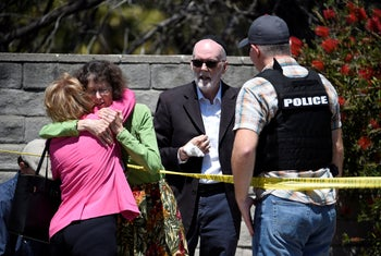 Two people hug as another talks to a San Diego County Sheriff's deputy outside the Chabad of Poway synagogue in Poway, California, April 27, 2019.