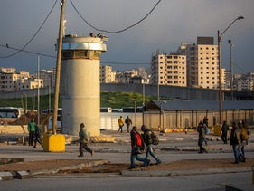 Palestinian workers cross into Israel at the Qalandiya checkpoint north of Jerusalem, March 27, 2019.