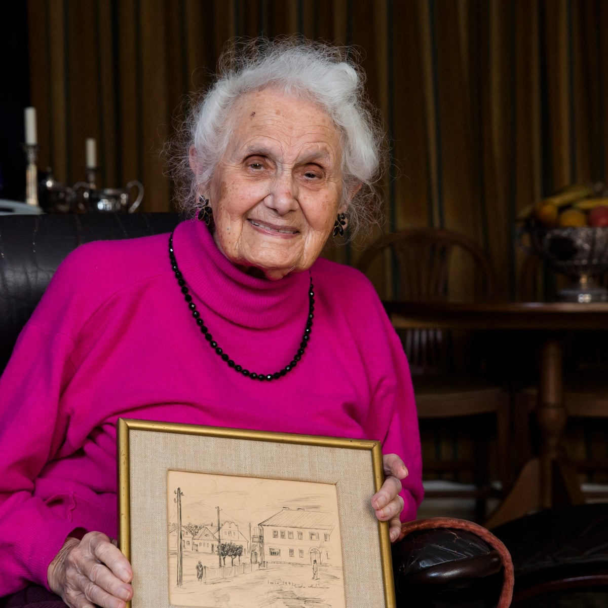 Tsiporah Singer, 96, holding a drawing  signed by a Wermacht soldier who helped save her life during the holocaust,  Netanya, Israel, 2019.