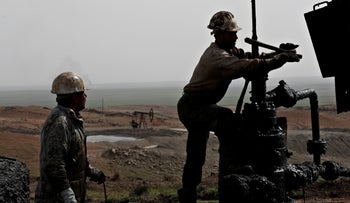 Syrian workers fixing pipes of an oil well at an oil field controlled by a U.S-backed Kurdish group, in Rmeilan, Hassakeh province, Syria, March 27, 2018.