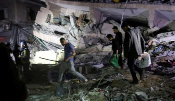 Residents inspect the damage of their destroyed multi-story building in Gaza City, Saturday, May 4, 2019