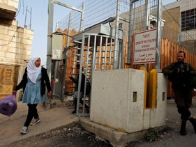 Palestinian schoolchildren cross through an Israeli checkpoint as they head to school, in Hebron, April 29, 2019.