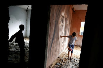 A boy plays football next to a mural painted by Palestinian artist Ali Al-Jabali in the remains of a building damaged during the 2014 war between Israel and Hamas, in Gaza City. April 30, 2019