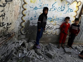 alestinian boys stand outside a mosque damaged in an Israeli air strike in Gaza City May 5, 2019
