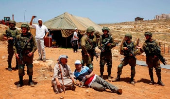 Palestinians sitting next to Israeli soldiers in front of a tent set up by settlers in Pnei Hever, in the West Bank, July 2018.