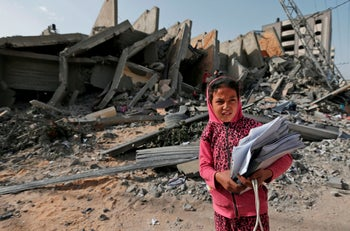 A Palestinians girl on May 6, 2019, stands in front of the rubble of a building that was destroyed during Israeli airstrikes on Gaza City. -