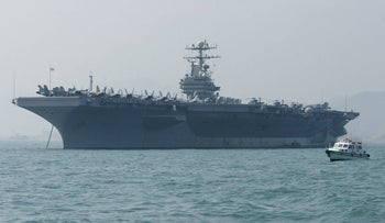 """In this file photo taken on December 23, 2004 A small boat sails by the USS Abraham Lincoln moored in Hong Kong. - The United States is sending an aircraft carrier strike group and a bomber task force to the Middle East in a """"clear and unmistakable"""" message to Iran, National Security Advisor John Bolton said May 5, 2019."""