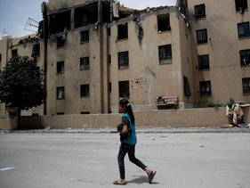 Palestinian girl walks by a house following a late night Israeli missile strike in town of Beit Lahiya, northern Gaza Strip, Monday, May. 6, 2019.