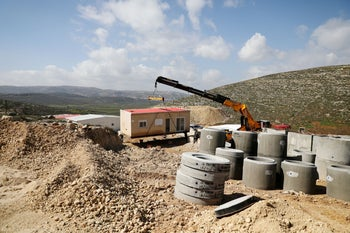 A crane lowers a caravan to the ground in Amichai, a new settlement which will house some 300 Jewish settlers evicted in February 2017 from the illegal West Bank settlement of Amona, on April 6, 2019.