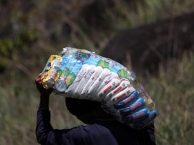 A Venezuelan man carries a bag of food as he tries to cross into Venezuela by the field at the border with Brazil in Pacaraima, Brazil February 26, 2019.
