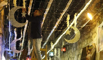 A Palestinian man decorates with lights near the entrance of the al-Aqsa mosque compound, in the old city of Jerusalem on May 4, 2019.