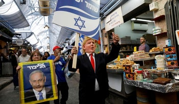 Likud party supporters, one wearing a mask depicting U.S. President Donald Trump, walk past stalls in Mahane Yehuda Market in Jerusalem April 7, 2019.