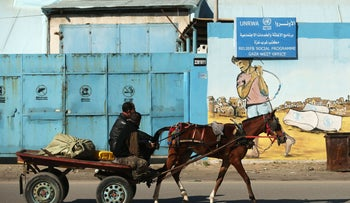 Palestinian man rides his horse past the UNRWA relief and social programme office in Gaza City, January 8, 2018.