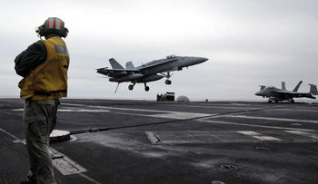 FILE PHOTO: a U.S. fighter jet lands on the USS Abraham Lincoln aircraft carrier during exercises in the Persian Gulf, 2012.