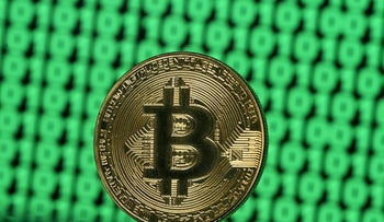 FILE PHOTO: A token of the virtual currency Bitcoin is seen placed on a monitor that displays binary digits in this illustration picture, December 8, 2017.