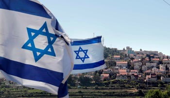 File photo: Israeli flags in front of a partial view of the Israeli settlement of Efrat in the West Bank, April 2019.