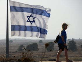 FILE PHOTO: A girl walks past an Israeli flag in the Golan Heights