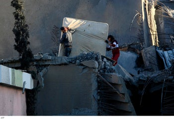 Palestinian men carry a mattress out from the rubble of a building that was destroyed by Israeli air strikes, in Gaza City, May 7, 2019.