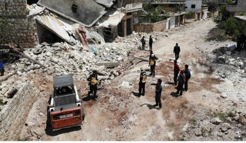 Members of the Syrian Civil Defence (White Helmets) clear rubble to open a road following reported shelling on the village of Ibdita in the Idlib province, May 8, 2019.