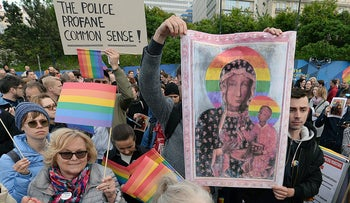 Participants in a protest hold copies of the posters and a giant rainbow flag in support of Elzbieta Podlesna, in Warsaw, Poland, May 7, 2019.