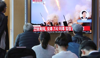 People watch a TV showing a file photo of North Korea's weapon systems during a news program at the Seoul Railway Station in Seoul, South Korea, May 9, 2019.
