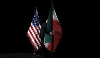 FILE PHOTO: A staff member removes the Iranian flag from the stage after a group picture with foreign ministers and representatives during Iran nuclear talks, Vienna, Austria, July 14, 2015.