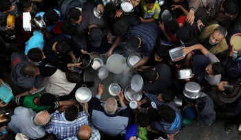Palestinians gather to get soup offered for free during the Muslim fasting month of Ramadan, in Gaza City May 9, 2019.