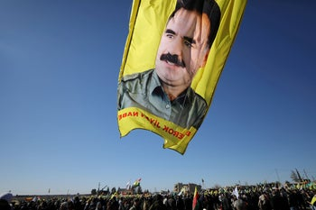 FILE PHOTO: A banner with a picture of imprisoned Kurdish rebel leader Abdullah Ocalan is seen during a protest against the Turkish attacks on Afrin in Qamishli, Syria January 30, 2018.