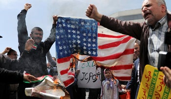 Iranian worshippers burn a representation of a U.S. flag during a rally after Friday prayer in Tehran, Iran. May 10, 2019
