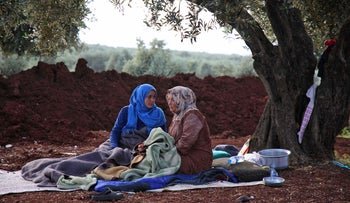 Displaced Syrians sit in a field near a camp for displaced people in the village of Atme, in the jihadist-held northern Idlib province, May 8, 2019.