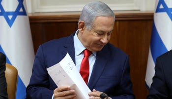 Israeli Prime Minister Benjamin Netanyahu holds a paper at the start of the weekly cabinet meeting at his Jerusalem office on May 12, 2019.
